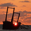 Sun rising behind wreck of the Polyxeni