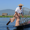 Inle Lake fisherman. He uses the metal trap on his boat to catch fish. by Benjamin
