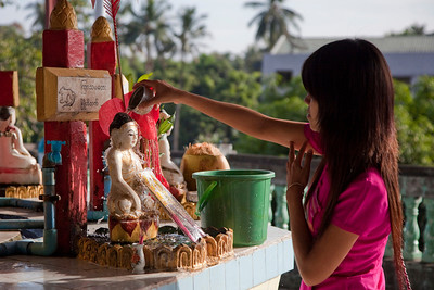 Woman pouring water over Buddha at Chaukhtatgyi Paya, Yangon