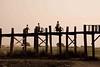 Bicyclists Walk on U Bein's (Teak) Bridge Mandalay. World's longest all-teak bridge. (1.2 km)
