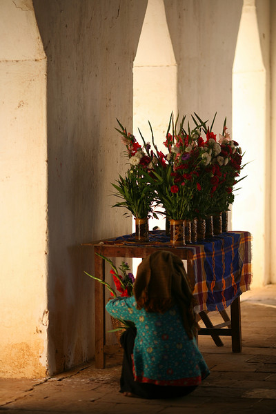 A worshiper leaves a flower offering at the temple entrance.