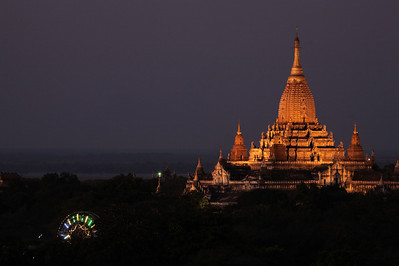 The temple is lit during the evening. Note the ferris wheel, part of the Ananda Festival market.