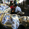 Bronze forgers touching up a now-reclining Buddha statue.