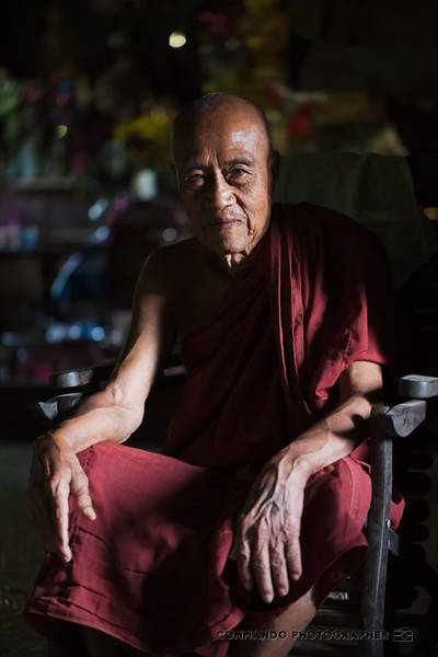 An old monk considers me as I shoot his portrait.