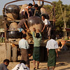 Men haul a large ceramic cistern onto the back of a truck.