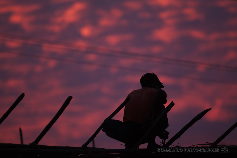 A worker is silhouetted against the sky as he puts the finishing touches on a roof.