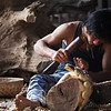 A wood carver skillfully chips away at a chunk of tree to reveal the bird inside.