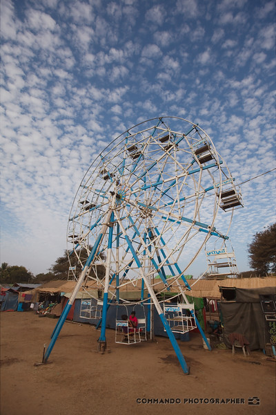 This Ferris wheel is not operated by electricity, but by young men climbing up through the bridgework and using their weight to set it spinning.