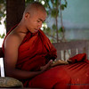 A young monk studies on the monastery grounds.