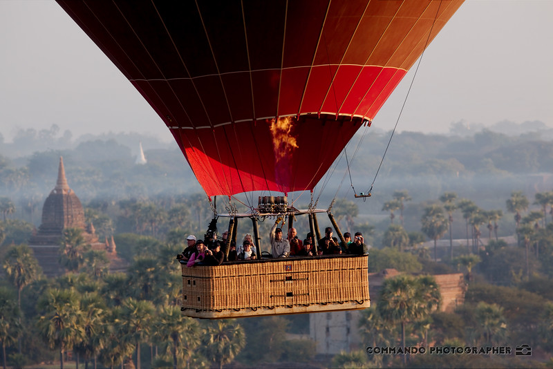 A basket full of tourists floats above the plain.