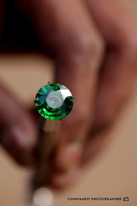 A vendor presents an emerald for purchase.