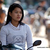 Astride her new motorbike, a young woman waits for a friend.