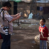 An Indonesian man takes a photo of a young boy.