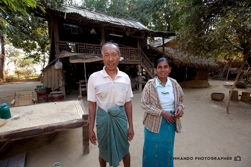 A couple pose before their village home.