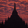 A temple is silhouetted against a burning sunset.