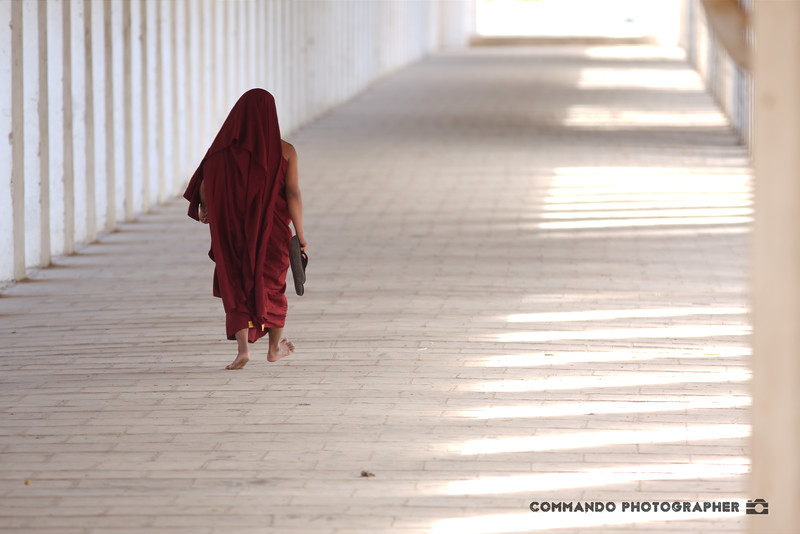 A monk makes his way beneath a covered walkway.