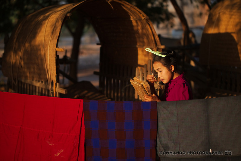 A woman in one of the village encampments applies makeup in preparation for going out.