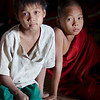 A young monk and his friend sit in the soft light of the monastery.