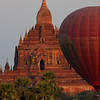 A hot air balloon drifts in front of a temple.