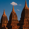 Three brick stupas stand out against the darkening sky.