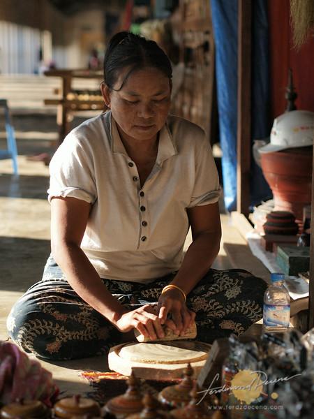 A lady grinding a thanaka bark