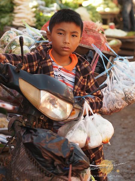 Boy on motorbike selling goods