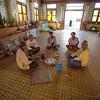 Gentlemen take tea on woven floor mats.