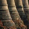 The lowering sun bounces from a row of stupas.