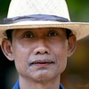 Gentleman in straw hat and betel nut stained lips.