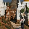 A worker continues his work on the crumbling stupas.