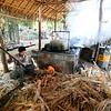Crushed sugar cane fuels the fire of a series of boiling vats.