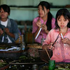 The young women sit in the soft light, their tools before them, creating cheroots.