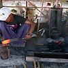A smith works on a farm tool.
