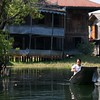 A woman paddles past a stately home on the lake.