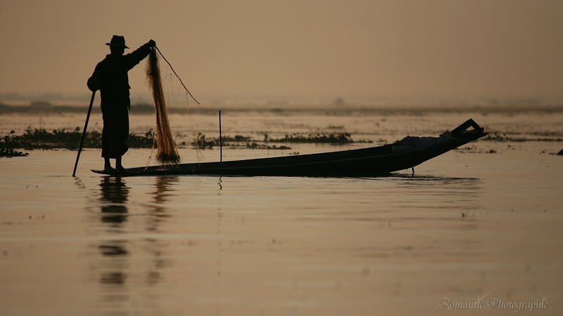 Standing at the end of his boat, the canoe rises in the front.