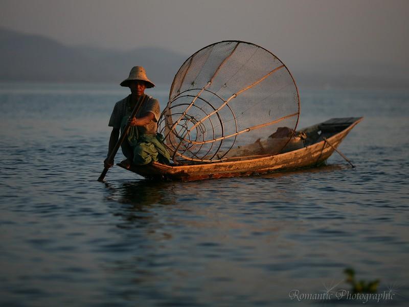 A man paddles his boat, the fishing trap basket balanced behind him.