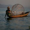 A man paddles his boat, the fishing trap basket balanced behind him.