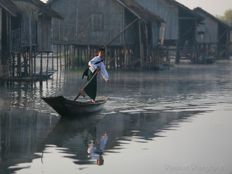 A boy goes to school by canoe.