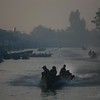 Long boats, laden with goods, make their way to the early morning market.