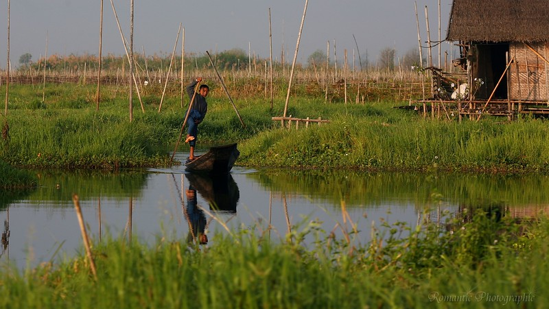 A young man maneuvers his canoe out through the floating gardens near his home.