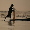 Using his leg around the paddle for balance, a fisherman prepares to cast his net.