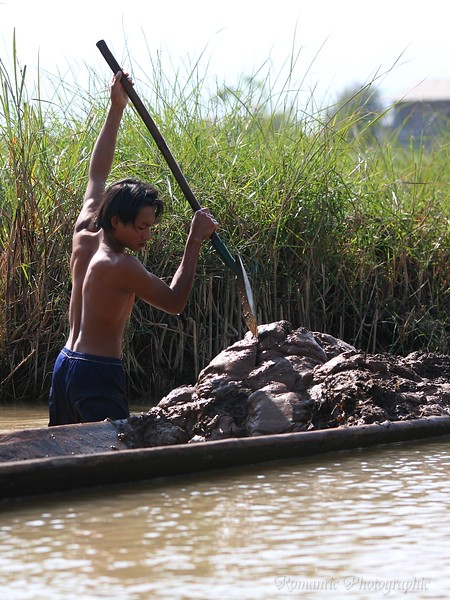 A man collects nutrient rich mud from the lake bottom.