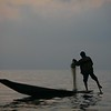 Balancing with his leg wrapped around his paddle, he prepares his fishing net.
