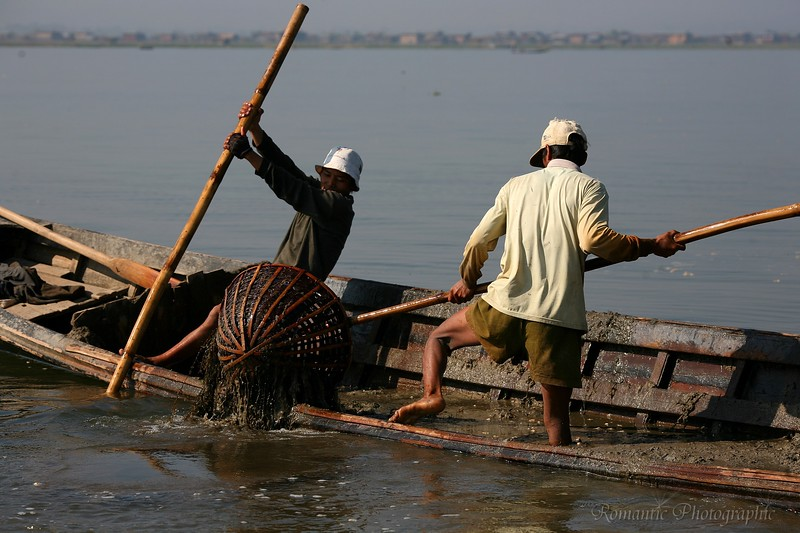 They load the boat with mud, a basket at a time.