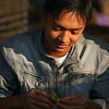 A young man prepares a betel nut for chewing.