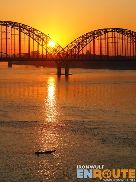 A small boat crossing over Irrawaddy River at sunset