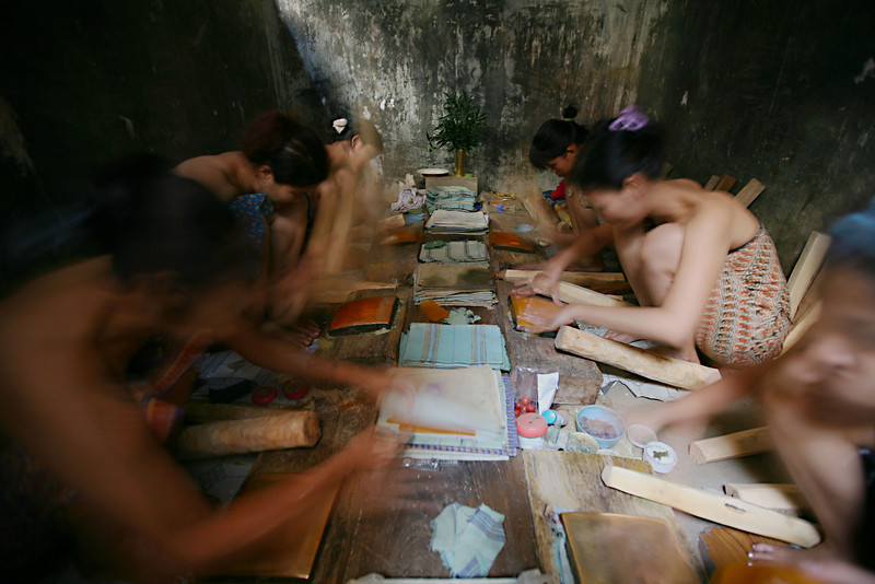 Bamboo sheets are prepared in a dark and very humid room by a group of women.