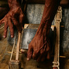 The gold is stacked between sheets of bamboo wrapped in leather, held together by bamboo and strapped against a stone.