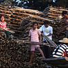 A small family loads a truck with split bamboo.
