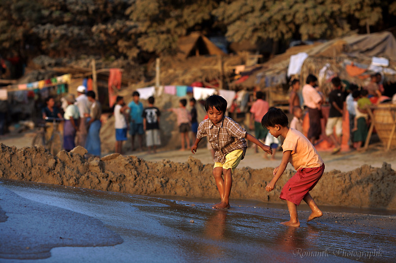 Children play in the fresh sand on the bank.